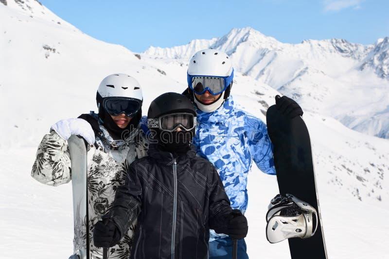 Stand de famille avec le snowboard et les skis image stock