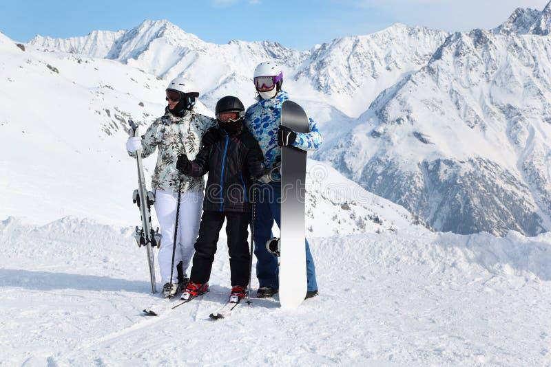 Stand de famille avec le snowboard et skis sur la montagne images libres de droits