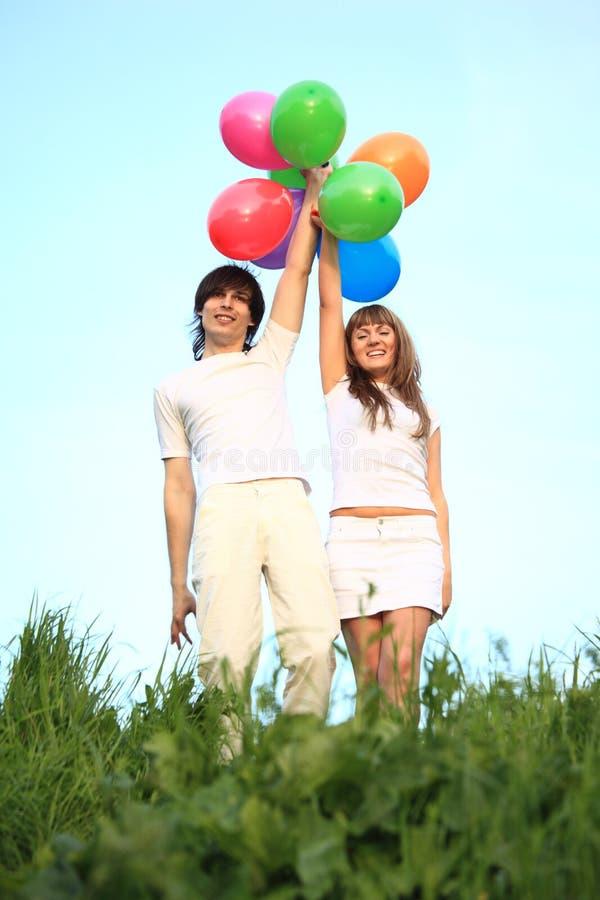 Stand de fille et de type avec les ballons multicolores images libres de droits