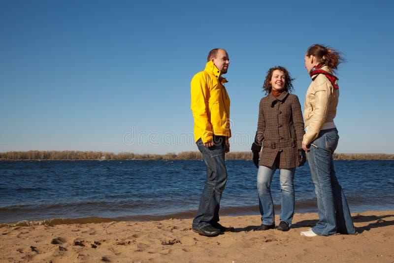Stand de trois jeunes hommes sur le côté du fleuve images stock