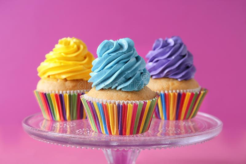 Stand with delicious birthday cupcakes on color background stock photos