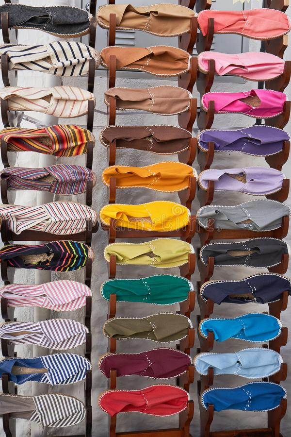 Stand with many fabric espadrilles of different colors. Stand with many cloth espadrilles of different colors in a small shop in Spain stock image