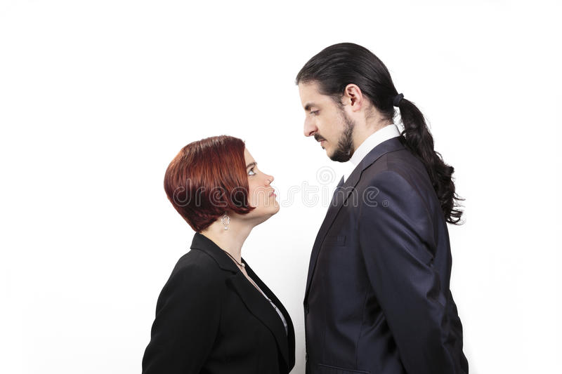 Stand off between a male and female partner. With the shorter women staring up belligerently into the face of the men in a suit with a ponytail, profile view on stock images