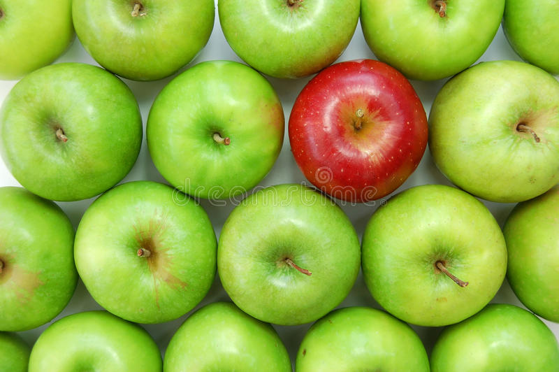 Stand out from the crowd. Red apple amongst many green ones stock photography