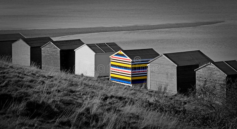 Stand out from the crowd. Photo of colourful striped beach hut in contrast against a black and white beach scene...depicting theme of contrasts,stand out