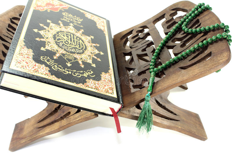 Stand with Quran and green rosary. Before light background stock image