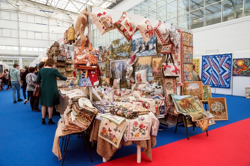 A stand with tapestries and embroidered items in the exhibition hall at the popular traditional urban fair of handicrafts. royalty free stock images