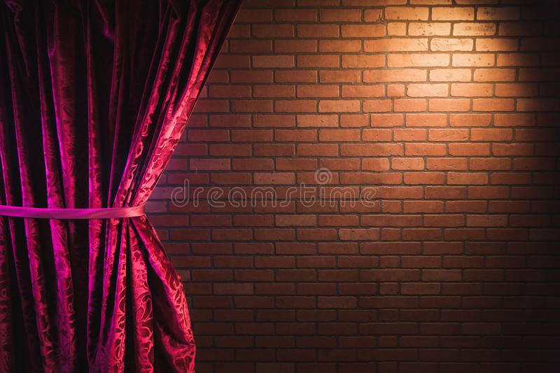 Brick wall and red curtain. Stand up comedy background, red curtain and a brick wall with a reflector spotlight, high contrast image stock images