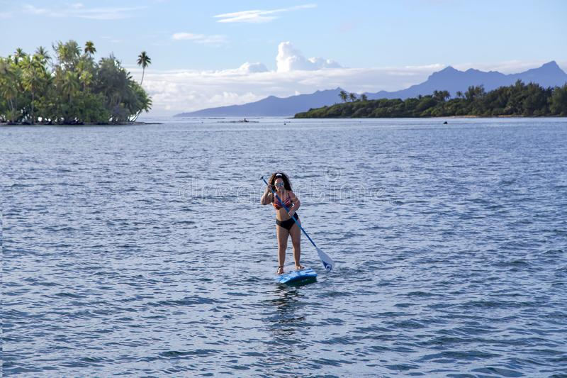 Stand up paddle board woman paddleboarding about the beautiful island of Tahaa royalty free stock image