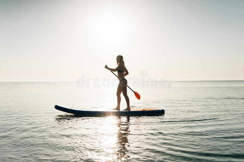 Stand up paddle board woman paddleboarding on Hawaii standing happy on paddleboard on blue water. stock photos
