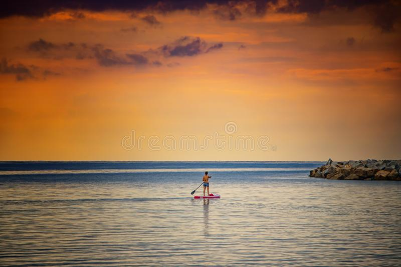 Stand Up Paddle Board Woman Silhouette on Water, Cagliari, Italy. Natural background with Mediterranean sea at sunrise, The sun. Illuminates the island with stock photo