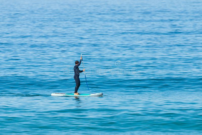 Stand up paddle boarder in wetsuit paddling on a sea. Minimalist image royalty free stock photos