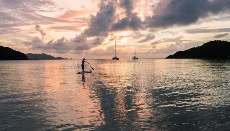 Beautiful blonde woman on stand up paddle board on holiday during sunset with yachts in the background in the Caribbean. royalty free stock photo