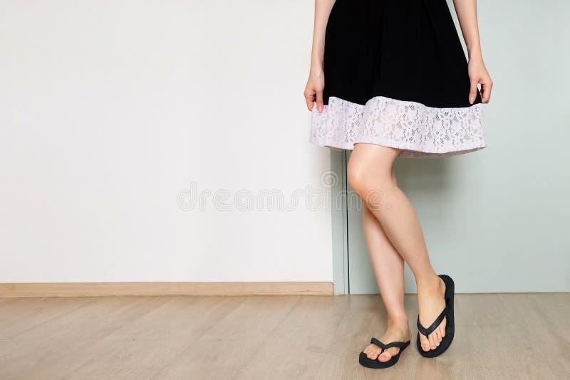 Stand-up wijfje Vrouw in Zwarte Kleding en Zwarte Schoenen Een Mooie Vrouw die zich op Houten in Witte Zaal Studio bevinden stock afbeelding