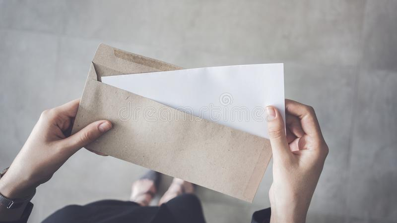 Stand up woman holding white folded a4 paper and brown envelope stock photography