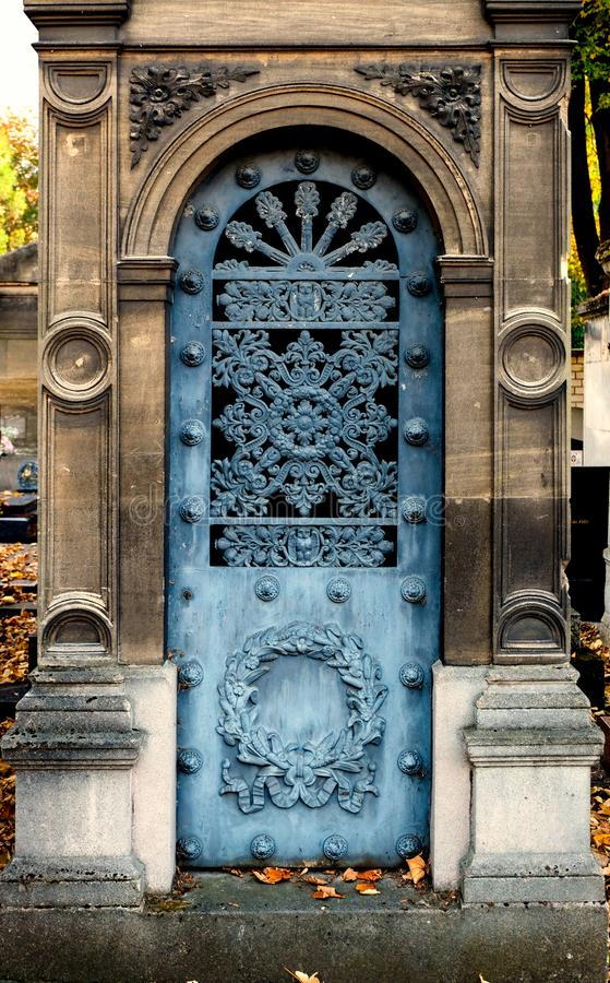Old blue iron entrance door of a tomb / crypt at a cemetery royalty free stock photography