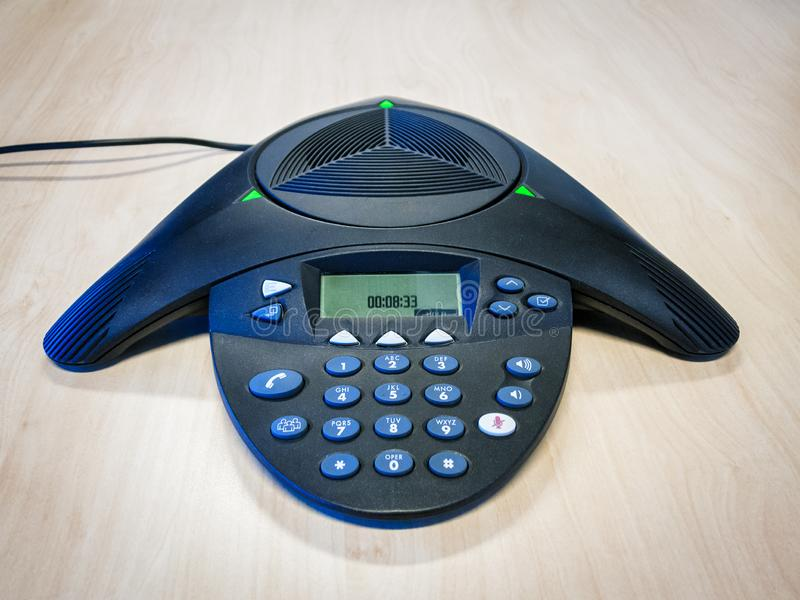 Conference call telephone on table. A standard desktop conference call speakerphone on a wooden table royalty free stock photos