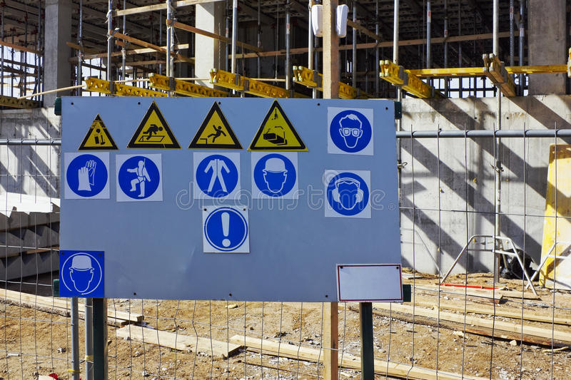 Standard warning signs on building. The metal stand with the standard warning signs of labor protection and health on building royalty free stock photo
