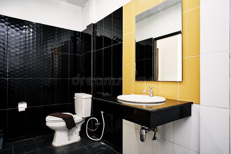 Standarda lättheter av generiskt toalettrum av liten hotell- eller lägenhetgarnering med glansigt keramiskt i svart- och gulingvä arkivbilder