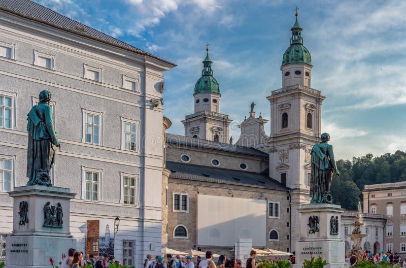 Standbeeld Mozart-Denkmal en de Kathedraal van Salzburg van Mozartplatz wordt gezien die stock afbeelding