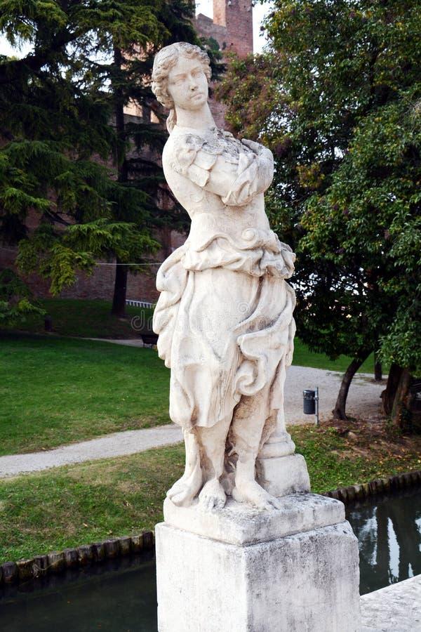 Standbeeld, rivier, bomen en straat in Castelfranco Veneto, in Italië stock afbeelding