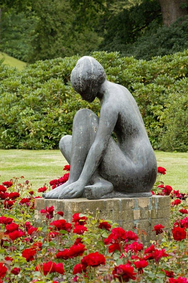 Standbeeld in roze tuin royalty-vrije stock afbeeldingen