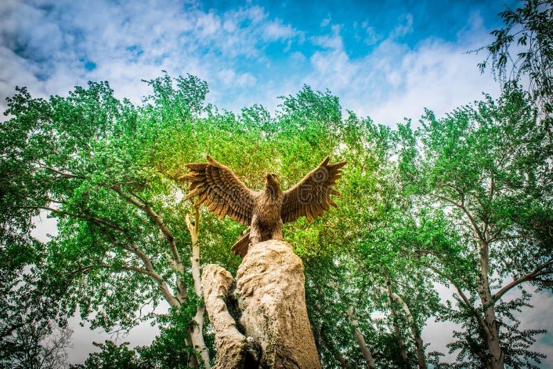 Standbeeld van een adelaar met open vleugels tegen een achtergrond van groene bomen en hemelmening van onderaan royalty-vrije stock afbeelding