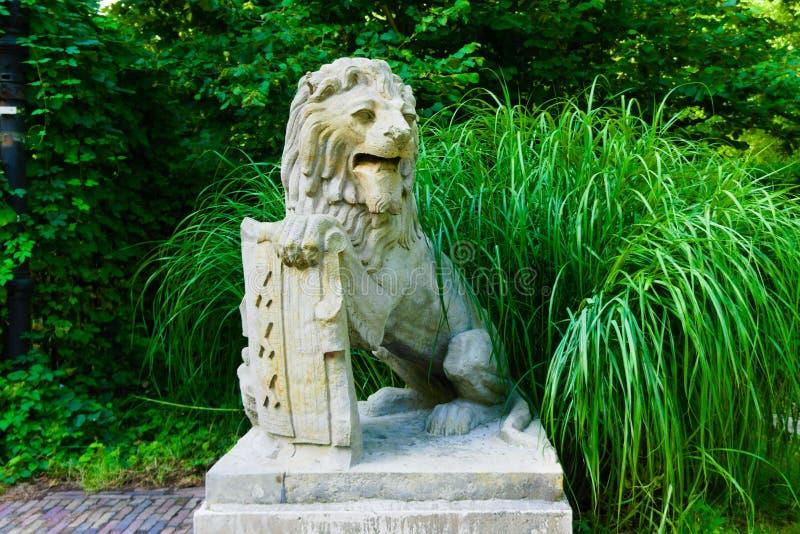Standbeeld van een leeuw die een schild houden stock foto's