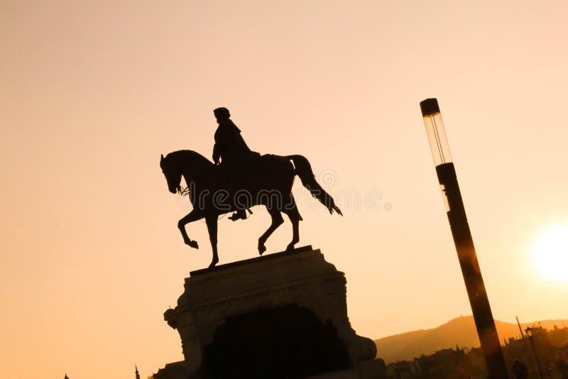Standbeeld van een mens op een paard in dynamische samenstelling, zonsondergang en mede stock foto's