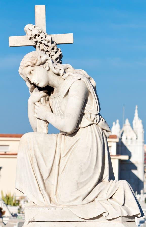 Standbeeld van een mooie jonge vrouw die een kruis houdt royalty-vrije stock afbeelding