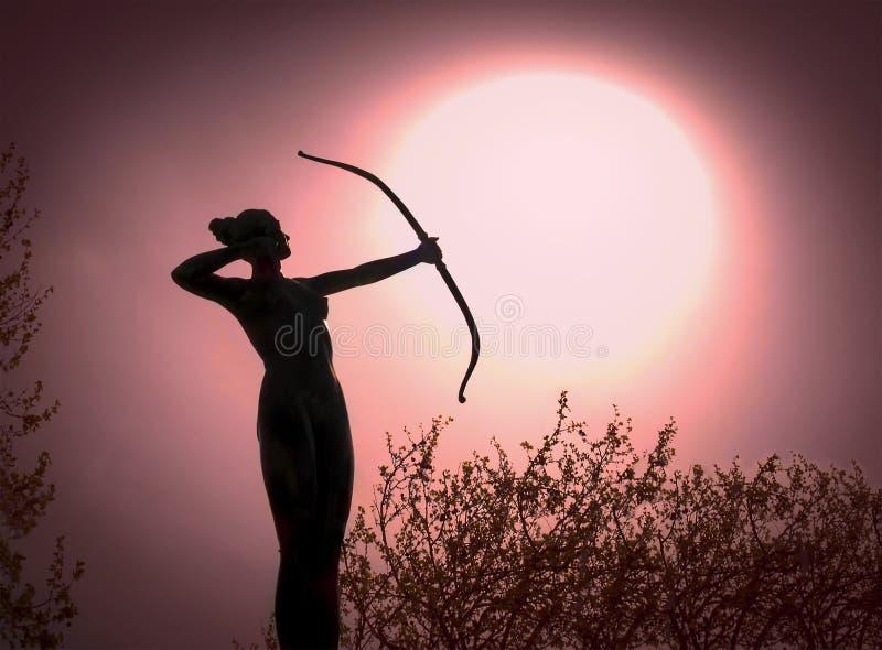 Standbeeld van een vrouw Archer Silhouette met een boogdoel de zon stock fotografie