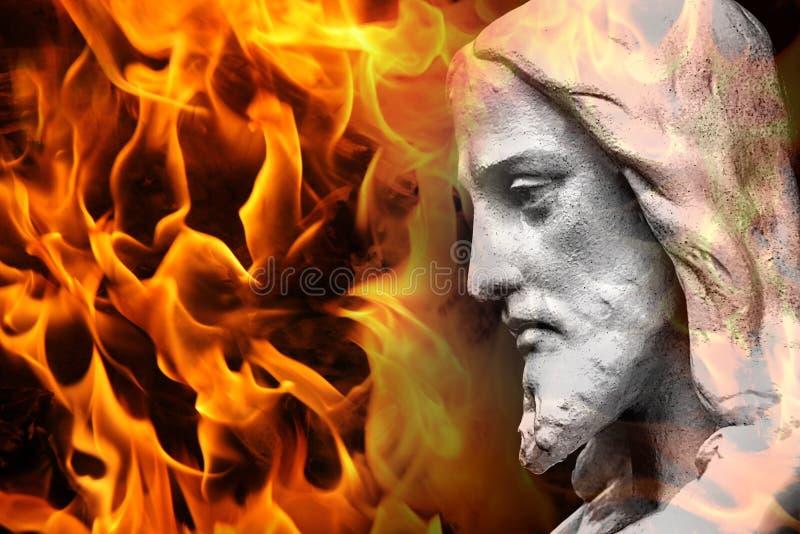 Standbeeld van Jesus/God met brand stock foto