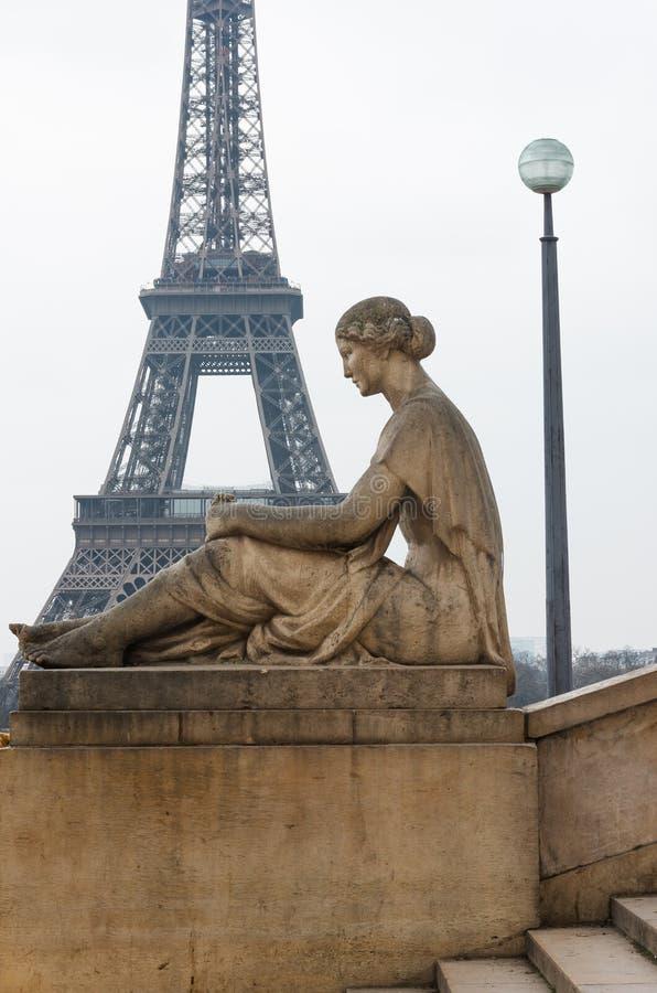 Standbeeld van van zittingsvrouw en Eiffel Toren royalty-vrije stock foto