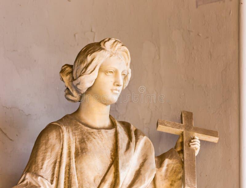 Standbeeld van vrouw met Christelijk kruis stock afbeeldingen
