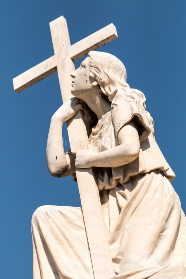 Standbeeld van vrouw met Kruis stock foto's