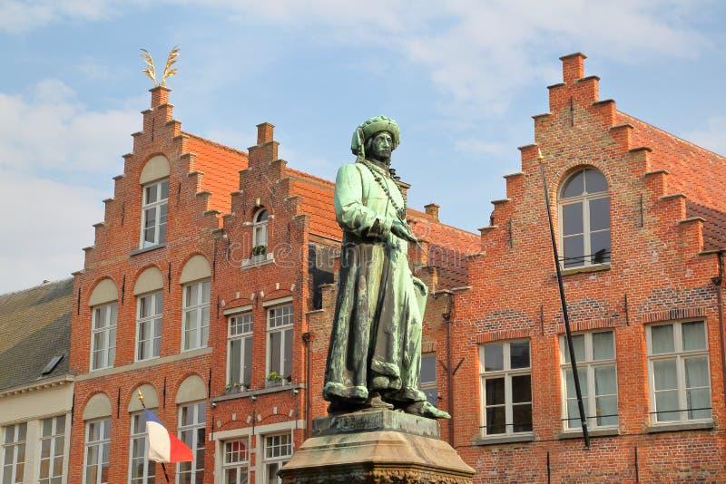 Standbeeld van Yan Van Eyck met erfenisgebouwen, in Jan Van Eyck Square, Brugge wordt gevestigd dat royalty-vrije stock afbeeldingen
