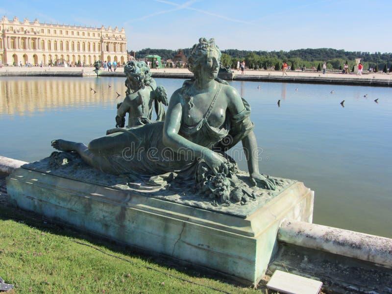 Standbeelden en sulptures in de Tuinen van Versailles met het Paleis van Versailles op de achtergrond frankrijk royalty-vrije stock afbeelding