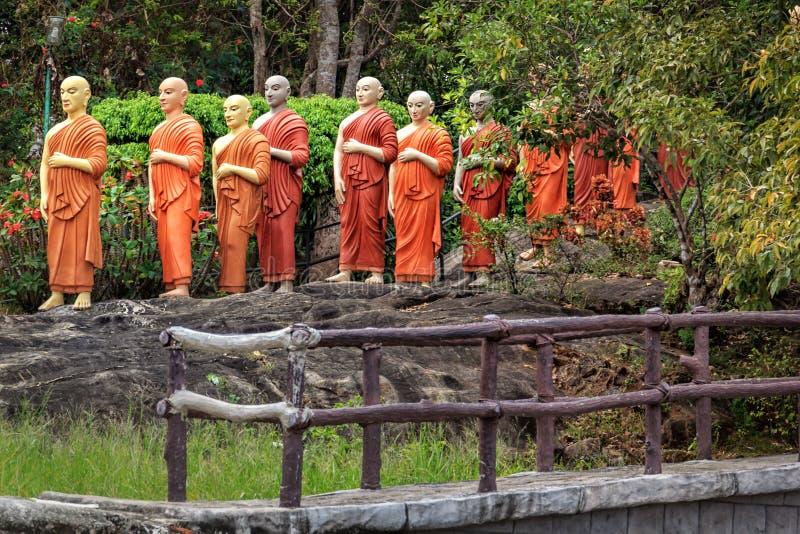 Standbeelden van Boeddhistische monniken die zich in lijn bevinden om Boedha te aanbidden royalty-vrije stock afbeeldingen