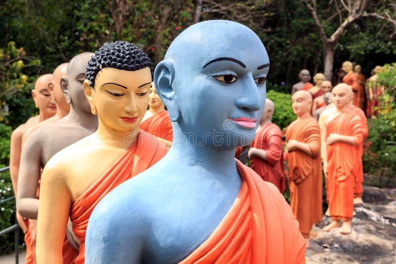 Standbeelden van Boeddhistische monniken die zich in lijn bevinden om Boedha te aanbidden royalty-vrije stock fotografie