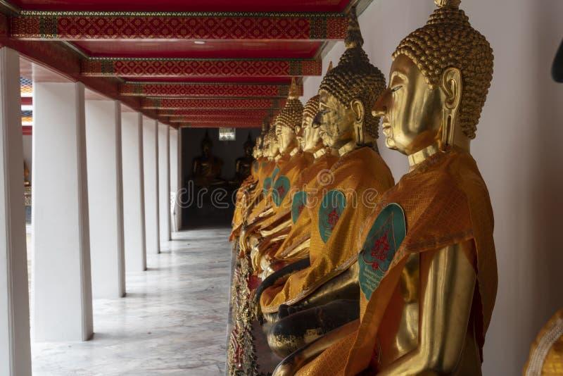 Standbeelden van het gouden buddhas bidden stock afbeeldingen