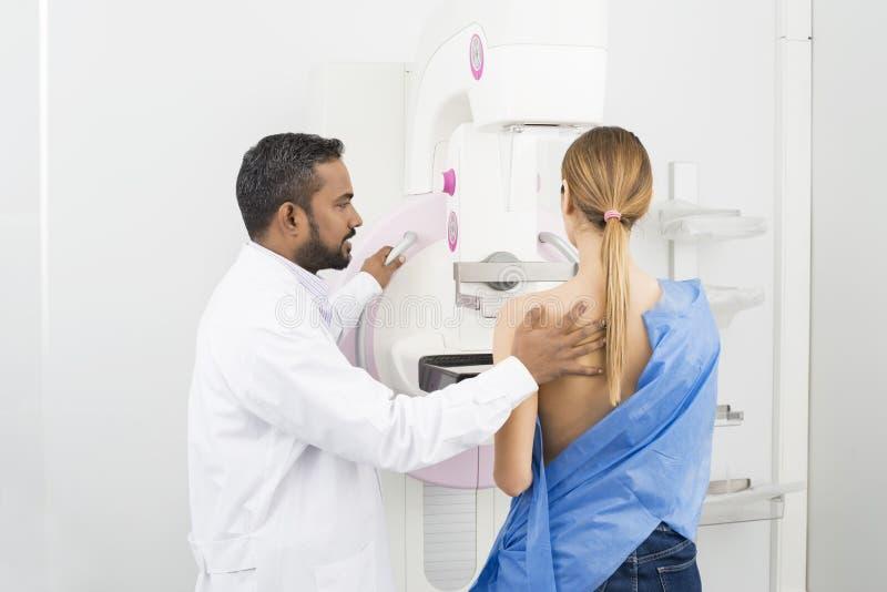 Standing Assisting Patient Undergoing医生乳房X线照片X-射线Tes 免版税库存图片