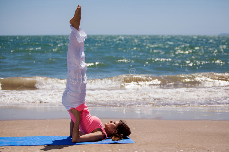 Standing on back and head. Pretty young woman doing some yoga at the beach and standing on her back and head stock photo
