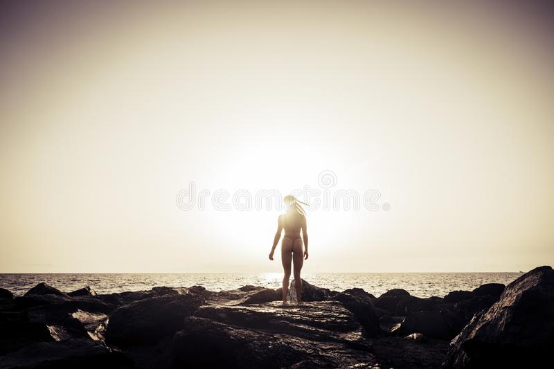 Standing back rear view portrait for fitness body young female enjoying the golden dark sunset at the rocky beach. horizon and. Quiet ocean in background. wind royalty free stock photo