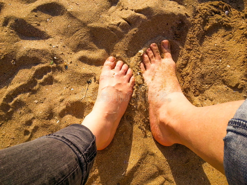 Standing barefoot on the beach top view. Sand texture. Standing barefoot on the beach royalty free stock images