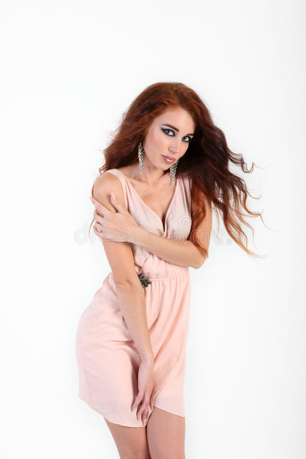 Standing beautiful young girl with red hair posing. With beige dress looking at camera royalty free stock images