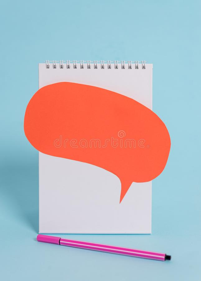 Standing blank spiral notepad speech bubble above pen lying cool pastel retro background. Empty text important future stock photo