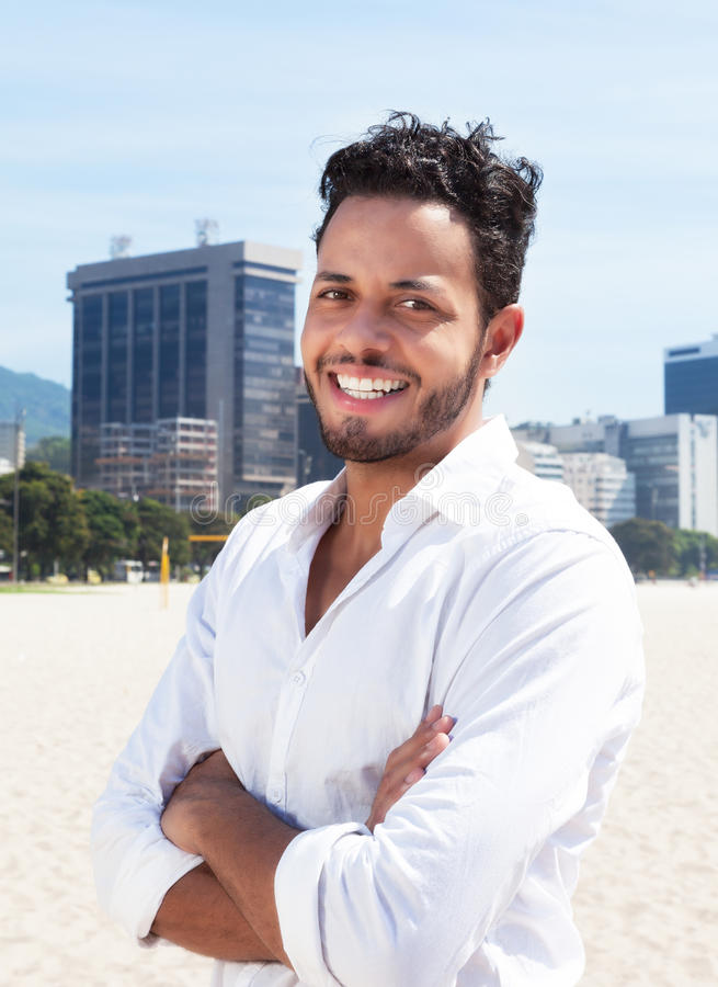 Standing brazilian man with skyline in the background. Standing brazilian man laughing at camera with blue sky and skyline of a modern city in the background royalty free stock photo