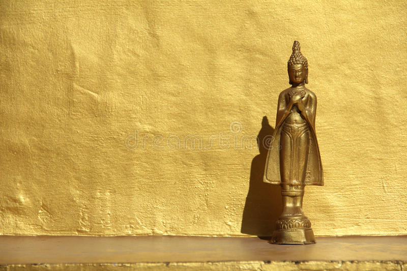 Standing Buddha Image And Golden Wall stock images