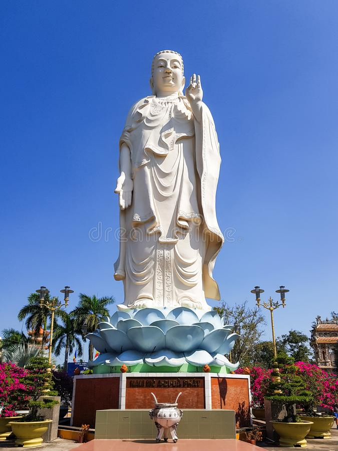 Standing Buddha Statue at the Vinh Trang Temple in Mytho City. Mekong Delta, Vietnam. stock photography