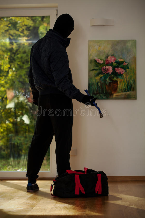Standing burglar in house. A standing burglar with a bag in front of a painting stock photos
